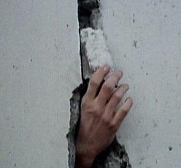 Po zneklidňujících úderech do zdi se z díry vynořila lidská ruka
