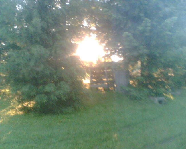 Východ slunce na pastvinách při pohledu od notebooku z okna