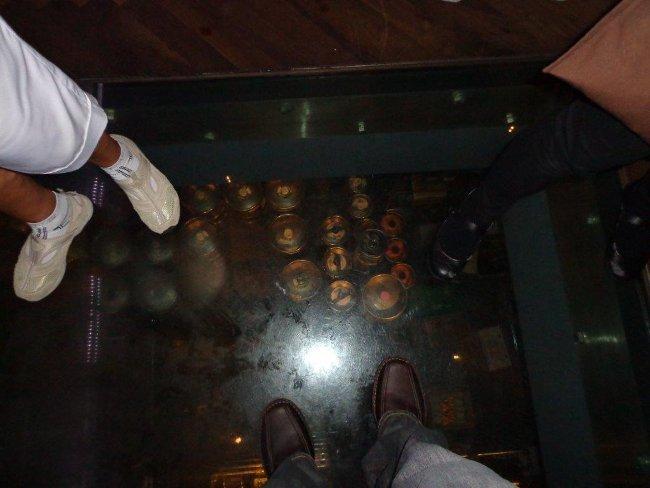"""Sklep plný sudů """"plzeňského"""" přes sklo podlahy"""
